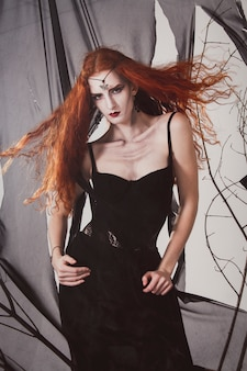 Donna rossa che una strega sta aspettando halloween. mago nero femmina dai capelli rossi