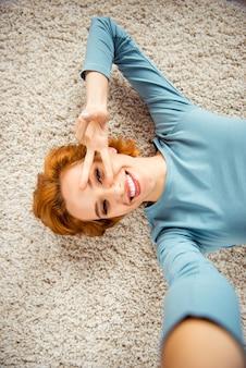Donna rossa con i capelli corti in posa al chiuso nel soggiorno