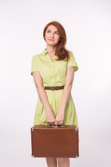 Giovane donna della testarossa che tiene retro valigia su priorità bassa bianca