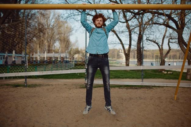 Il giovane di reds in abbigliamento casual si alza sulla barra nel parco