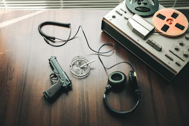 Registratore a bobina per intercettazioni telefoniche. conversazioni di spionaggio del kgb. pistola nera nelle vicinanze. posacenere con una sigaretta.