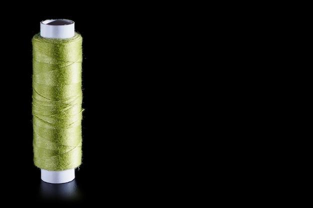 Bobina con fili di seta per cucire verdi isolati su uno sfondo nero, close-up, copia dello spazio