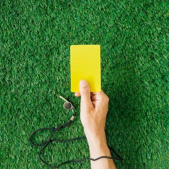Concetto dell'arbitro con la mano che tiene cartellino giallo