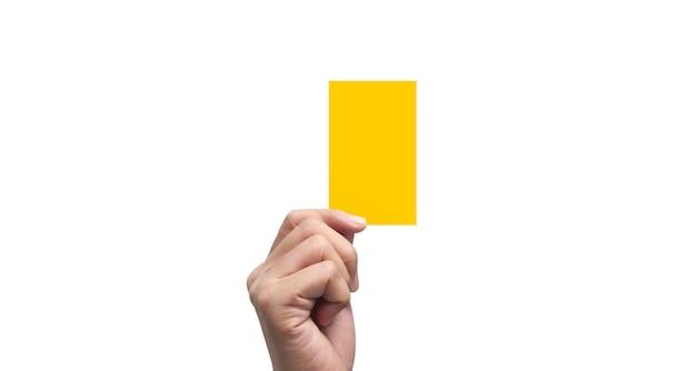 Mano dell'arbitro che tiene i cartellini gialli. isolato