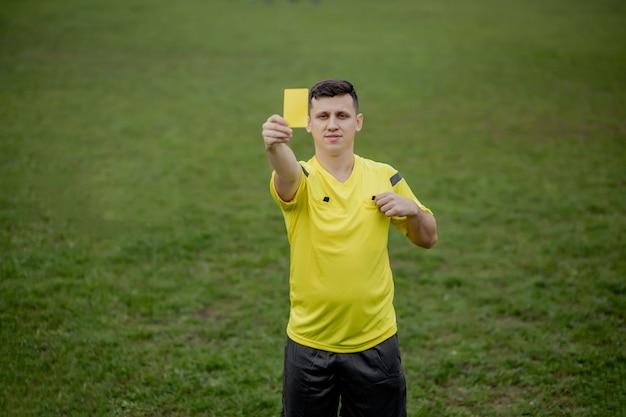 Arbitro che mostra un cartellino rosso a un calciatore dispiaciuto durante il gioco.