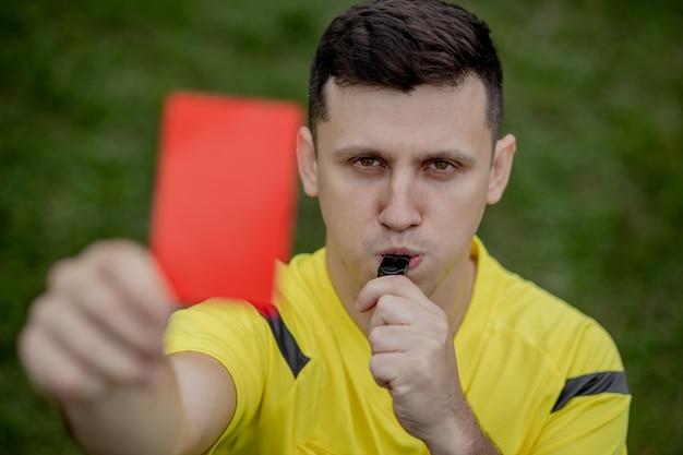 Arbitro che mostra un cartellino rosso a un calciatore dispiaciuto durante il gioco