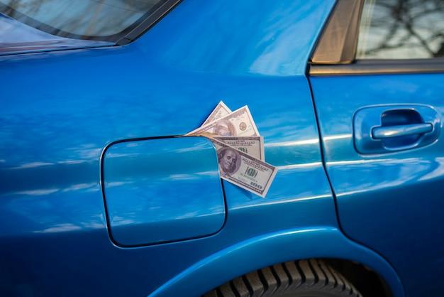 La ricarica dell'auto con carburante un po' di soldi in contanti all'interno del serbatoio del carburante idea di benzina costosa
