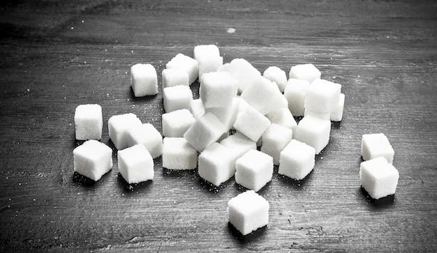 Zollette di zucchero raffinate. sulla lavagna nera.