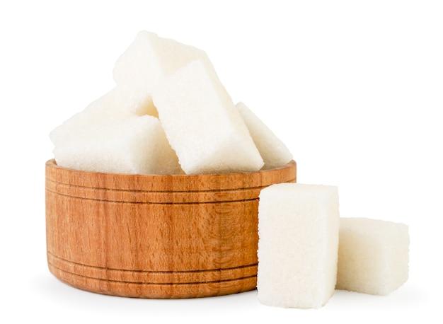 Zucchero raffinato in fine piatto di legno su isolato