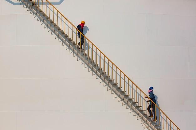 Operaio di fabbrica di raffineria salendo le scale metalliche su un edificio industriale del serbatoio dell'olio.