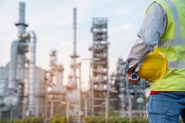 Ingegnere dell'industria della raffineria che indossa dpi al cantiere della raffineria