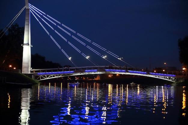 Illuminazione notturna riflessa del ponte nel fiume