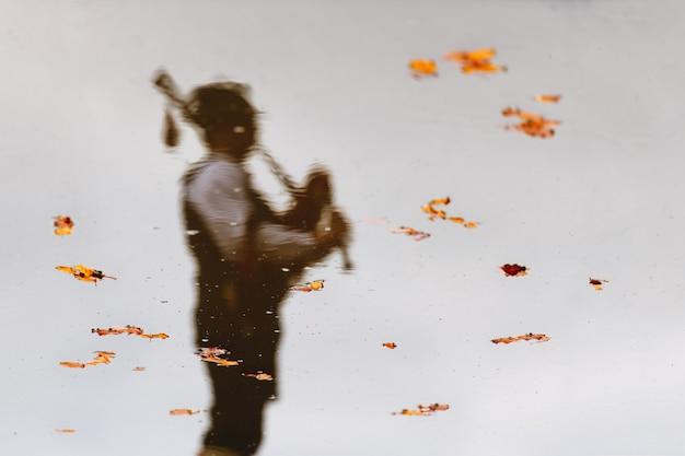 Riflesso in acqua con foglie di un suonatore di cornamusa
