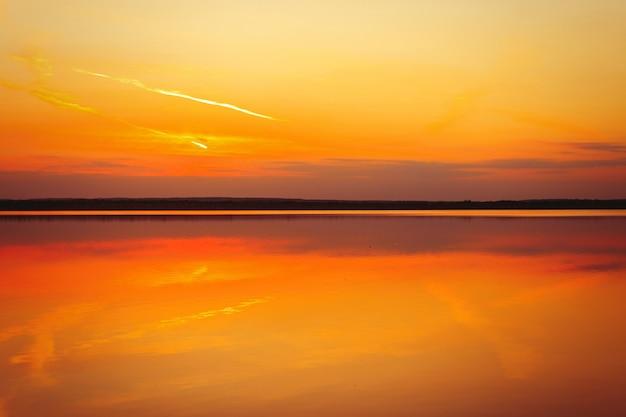 Riflessione di un bellissimo tramonto dorato sull'acqua