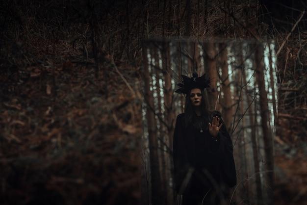 Riflessione di una strega terribile nera in uno specchio in una foresta oscura