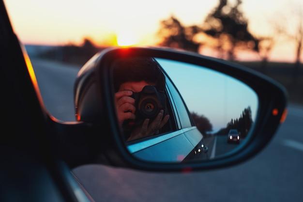 Riflessione nello specchietto retrovisore del giovane ragazzo che cattura foto del tramonto con la fotocamera digitale.