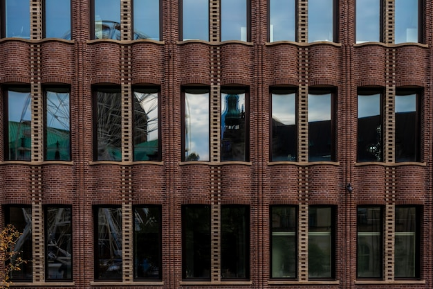 Riflesso della città nel vetro di un edificio industriale storico.