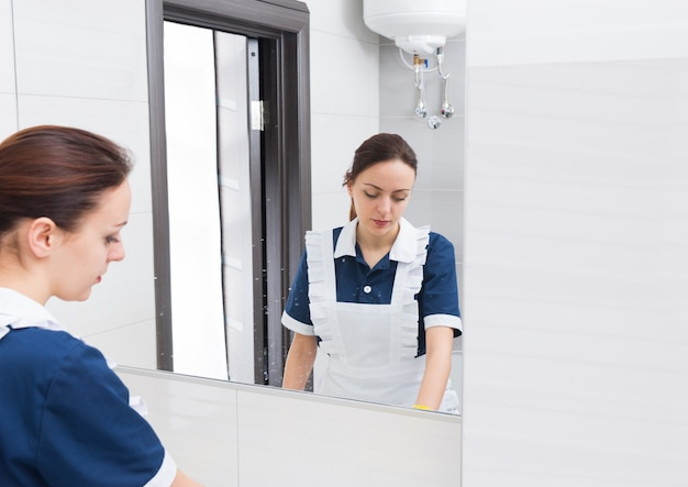 Riflessione della donna delle pulizie che indossa l'uniforme bianca e blu nello specchio mentre pulisce il bagno