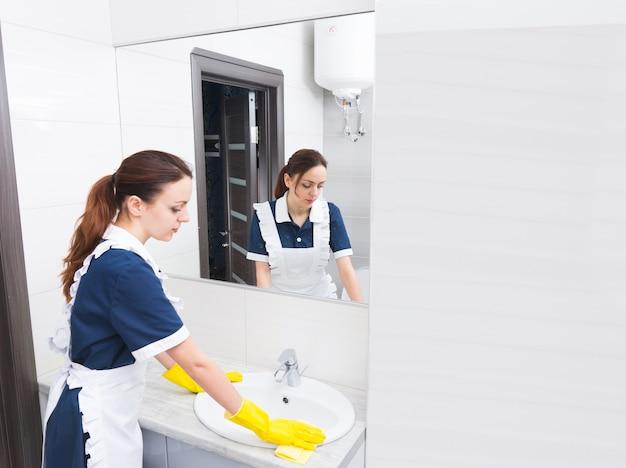 Riflessione della lavoratrice domestica che indossa guanti di gomma gialli e lavandino per la pulizia uniforme bianco e blu in bagno