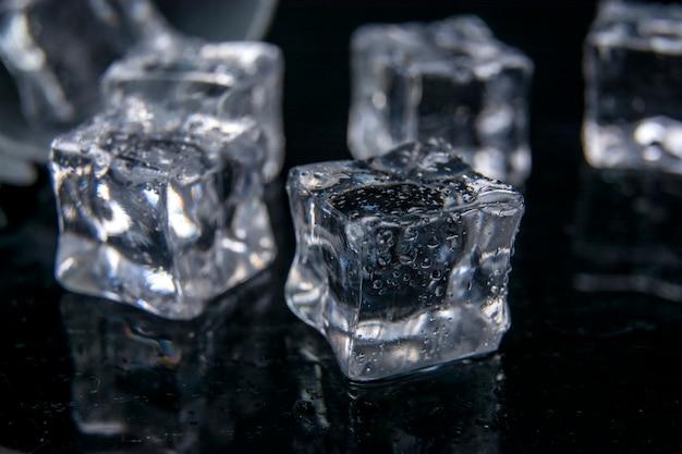Riflessione di cubetti di ghiaccio sullo sfondo nero del tavolo