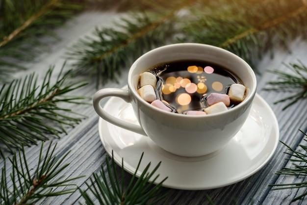 Riflessione di luci di ghirlande festive in una tazza di caffè con marshmallow. una tazza di caffè sul tavolo tra i rami di abete. concetto di vacanze di natale.