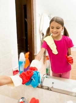 Riflessione nello specchio di una ragazza sorridente con le trecce che pulisce il bagno