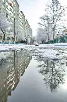 Riflessione sulla pozzanghera di paesaggi innevati invernali della città.