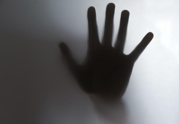 Riflessione delle ombre delle mani dei bambini su vetro smerigliato, sfocatura.