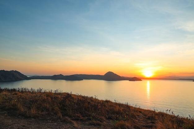 Riflessione del sole sul mare con silhouette di colline a labuan bajo