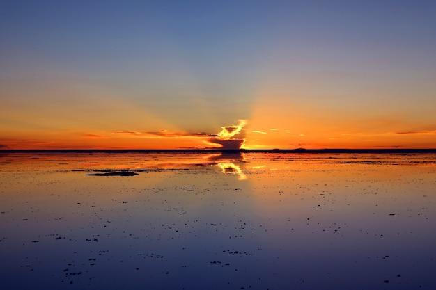 Riflesso del cielo al tramonto sulle saline inondate l'iconico effetto specchio a salar de uyuni bolivia