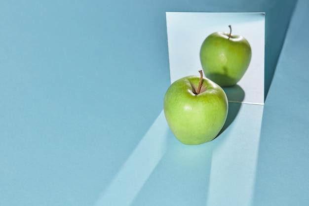Riflessione di un'intera mela verde nello specchio e nell'ombra