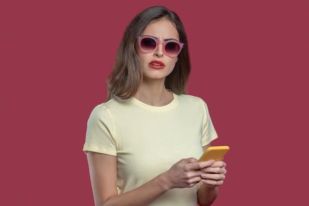Riflessi. grave giovane donna graziosa con labbra rosse in occhiali da sole e maglietta con smartphone giallo nelle sue mani