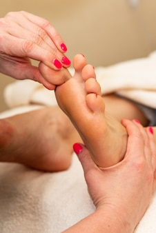 Massaggio di riflessologia plantare. riflessologo che fa pressione sull'alluce del cliente in un centro benessere