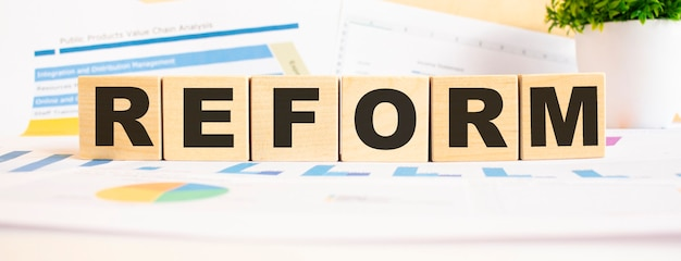 Parola di riforma sui cubi di legno. lo sfondo è un grafico aziendale. concetto di affari e finanza