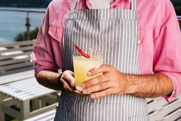 Cocktail rinfrescante. cameriere barbuto che indossa la camicia rosa normale portando cocktail rinfrescante con pepe piccante