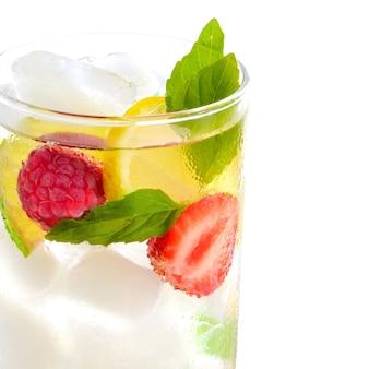 Cocktail rinfrescante con menta verde, lime, limone e frutti di bosco su sfondo bianco