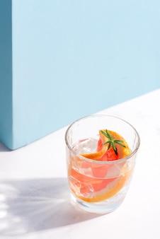 Bevanda fredda estiva rinfrescante in un bicchiere con fetta di pompelmo e cubetti di ghiaccio