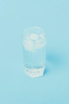 Acqua fredda rinfrescante con ghiaccio in un bicchiere su una superficie blu.