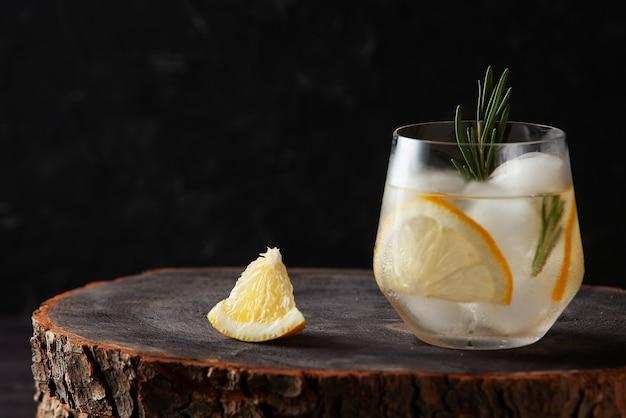 Bevanda rinfrescante con rosmarino al limone e ghiaccio su fondo di legno scuro
