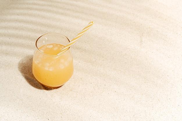 Bicchiere rinfrescante di succo di frutta con paglia sulla sabbia della spiaggia tropicale con ombre di foglie di cocco