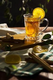 Tè freddo rinfrescante in un bicchiere con limoni a fette e due bastoncini di cannella su tavola di legno