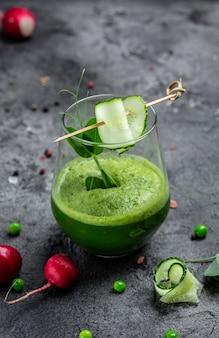 Frullato rinfrescante di verde di cetriolo di cavolo riccio in un bicchiere su sfondo di cemento. frullato detox, piselli freschi, cetriolo, ravanello, spinaci e lime. immagine verticale. vista dall'alto.