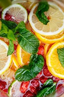 Limonata rinfrescante con frutta fresca arancia limone ciliegia e foglie di menta. delizioso cocktail di frutta analcolico in caraffa