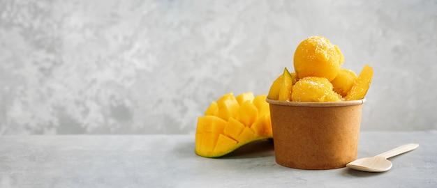 Gelato di rinfresco del mango in una tazza di carta di carta su fondo grigio