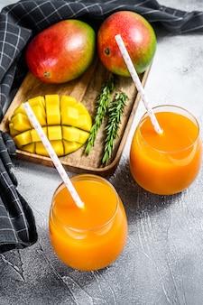 Succo di mango rinfrescante in un bicchiere. sfondo grigio.