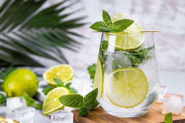 Mojito rinfrescante con menta lime e ghiaccio in un bicchiere su uno sfondo estivo