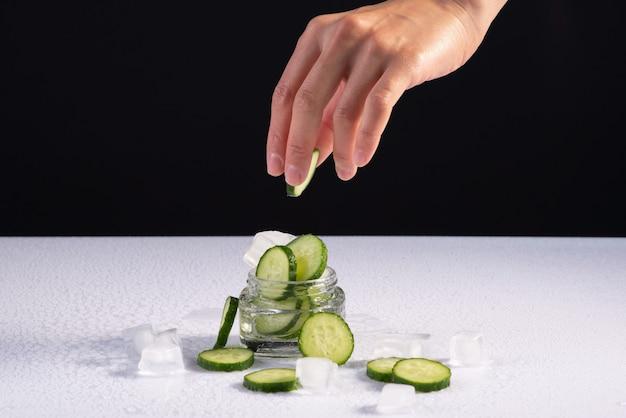 Cosmetici naturali rinfrescanti per le mani con estratto di cetriolo in contenitore di vetro con cubetti di ghiaccio su sfondo bianco e nero.