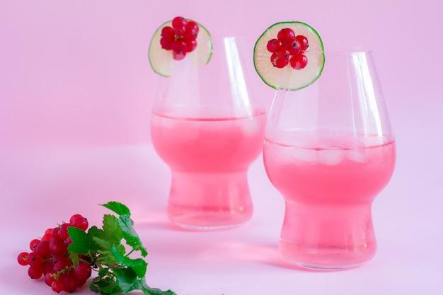 Limonata rinfrescante ai frutti di bosco rosa con lime su sfondo rosa
