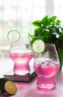 Limonata rinfrescante alla bacca rosa con lime sul tavolo con una pianta e una finestra sullo sfondo