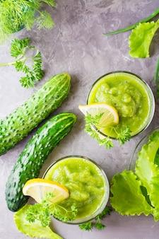 Frullati rinfrescanti da cetriolo, mela verde, erbe fresche e succo di limone in bicchieri trasparenti sul tavolo. il concetto di una dieta sana. menu vegetariano. vista dall'alto